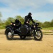 Two armed men riding a motorcycle with a sidecar. Motion blur. — Stock Photo #10721595