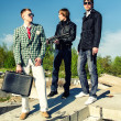 Mafia: Three thugs with a suitcase and weapons — Stock Photo