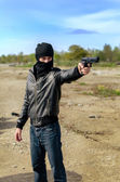 Masked gunman taking aim with a gun — Stock Photo
