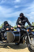 Two armed men riding a motorcycle with a sidecar — Foto de Stock
