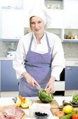 Attractive chief cook preparing food — Stock Photo