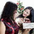 Girl gives another girl a gift for Christmas — Stock Photo