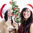 Christmas: two girls in red hat have fun — Stock Photo