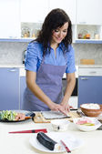 Portrait of pretty Chief cook in the kitchen. Sushi making. — Stock Photo