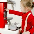Little cute girl playing in children's kitchen. — Stock Photo