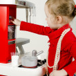 Little cute girl playing in children's kitchen. - Stock Photo