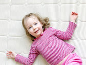 Cute little girl lying on a mattress — 图库照片