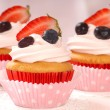 Royalty-Free Stock Photo: Vanilla cupcakes with stawberry frosting and strawberries and bl