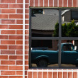 Brick wall with window and reflection of truck — Stock Photo