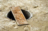 Unsecured sewer manhole — Stockfoto