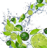 Limes in splash — Stockfoto