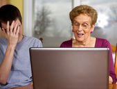 Grandson and grandmother at a laptop — Stock Photo
