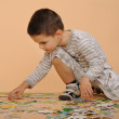 Boy collects puzzles — Stock Photo