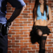 Stock Photo: Police officer delay prostitute