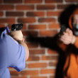 Stock Photo: Police officer and criminal targeting them at each other