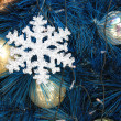 Snowflake ornament on blue christmas tree — Stock Photo