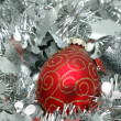 Christmas ball over silver garland — Stock Photo