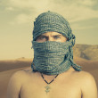 Brutal man in desert — Stock Photo