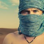 Brutal man in desert — Stock Photo