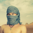 Brutal man in desert - Stock Photo