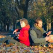 Couple of young musicians sitting in the ground — Stock Photo #10031410
