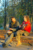 Couple of young musicians sitting in the ground — Stock Photo
