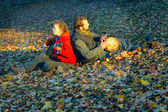 Couple of young musicians sitting in the ground — Stock fotografie