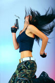 Girl with gun in jump action — Stock Photo