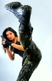 Girl with gun in kick moving — Stock Photo