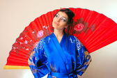 Girl in blue asian bathrobe with dragons — Stock fotografie