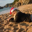 Woman on the beach wearing santa's hat — Stock Photo