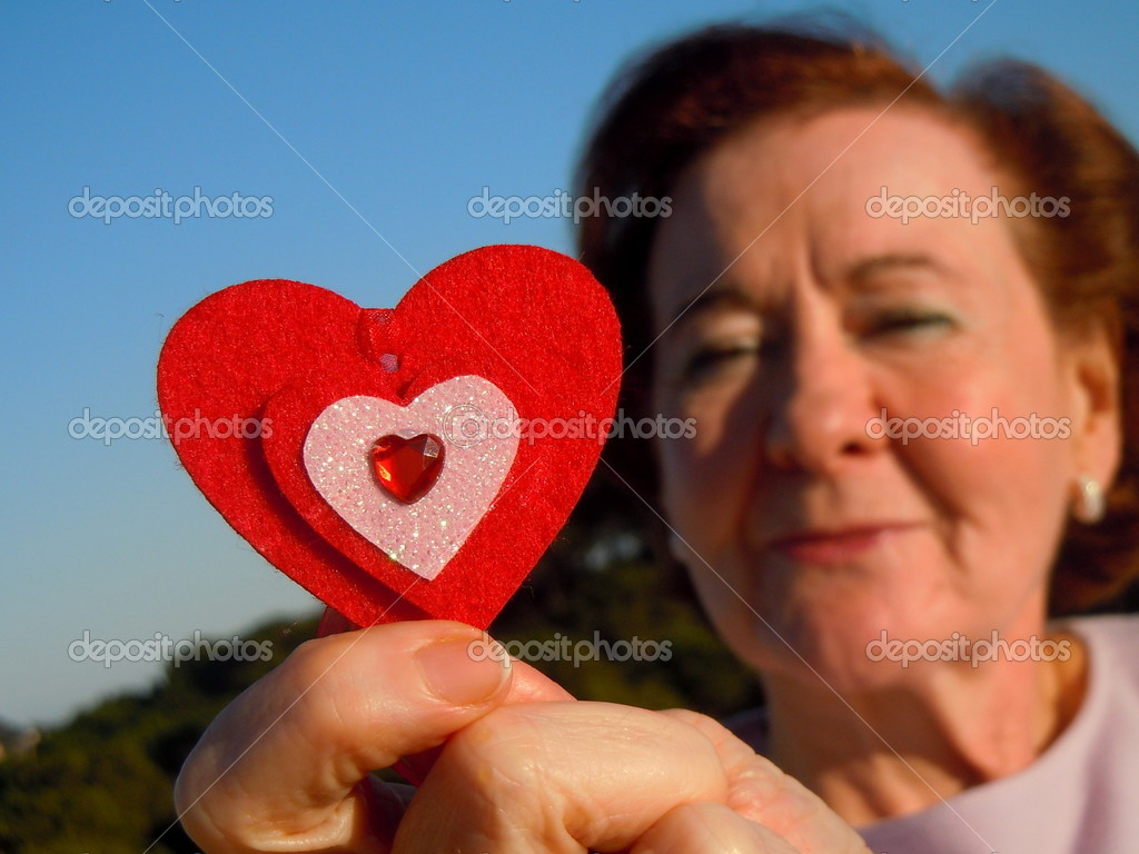 Senior woman and red heart, focus on heart — Stock Photo #8316852
