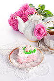 Сake with roses and cup of tea — Stock Photo