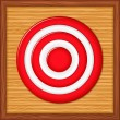 Red target on wooden background — Stock Vector