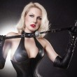 A young blond lady mistress with bright red lips without any emotions standing in a pose, wearing a black leather corset and gloves on the black background with the white flash light behind the model — Stock Photo #10259768