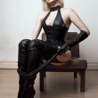 A young blond sexy lady mistress with bright red lips wearing a black leather corset in 18th century settings - Stock Photo
