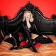 A young blond sexy lady mistress with bright red lips wearing a black leather costume — Stock Photo #10259951