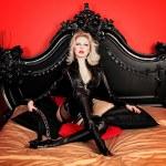 une maîtresse de la jeune dame sexy blonde avec des lèvres rouges vives vêtu d'un costume de cuir noir — Photo #10259951