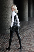 A young blond lady mistress with bright red lips in a white shirt without any emotions wearing a black leather corset and gloves and trousers light behind the model in the streets — Stock Photo