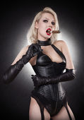A young blond lady mistress with bright red lips without any emotions standing in a pose, wearing a black leather corset and gloves on the black background with the white flash light behind the model — Stock Photo