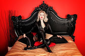 A young blond sexy lady mistress with bright red lips wearing a black leather costume — Stock Photo