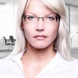 Young attractive business women smiling wearing glasses holding a folder in an office environment — Stock Photo
