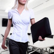 Young attractive blonde business women serious wearing glasses holding a folder in an office environment walking — Stock Photo
