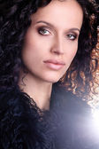 Portrait of a young Brazilian fashion glamour model and green eyes wearing fur playing with dark brown curly hair — Stock Photo