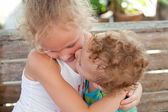 Younger brother kisses the cheek of his older sister — Stock Photo