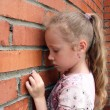 Sad child with a brick wall - Stockfoto