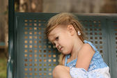 Sad little child on a bench — Stock Photo