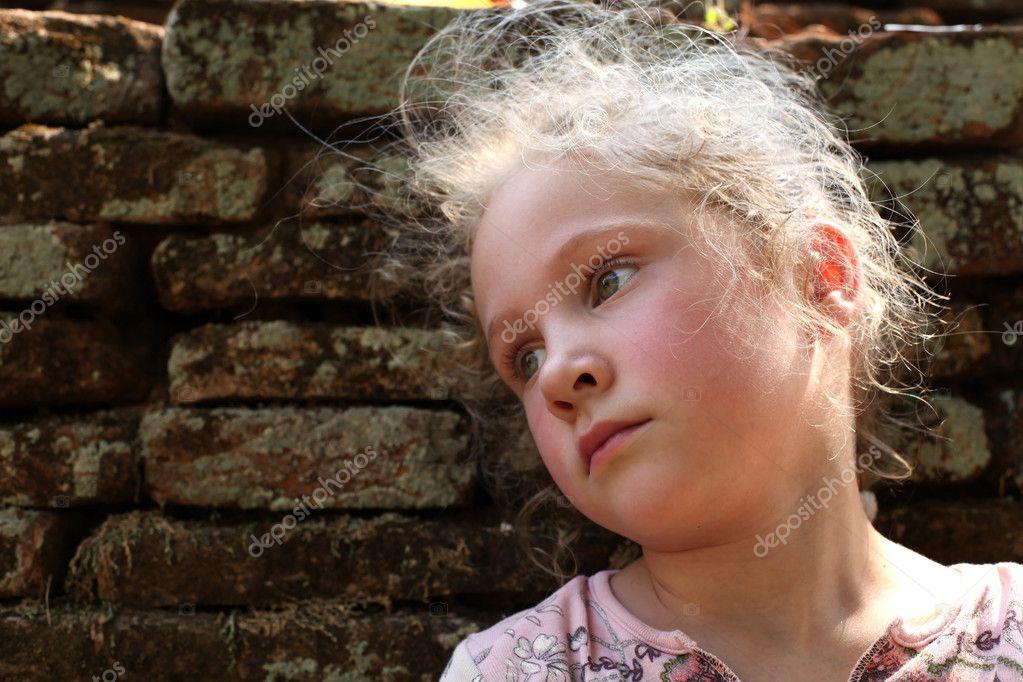 悲伤的小女孩的旧砖墙背景