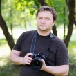 Man with professional digital camera - Stock Photo