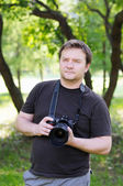 Man with professional digital camera — Stock Photo